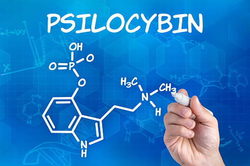 hand with pen drawing the chemical formula of psilocybin