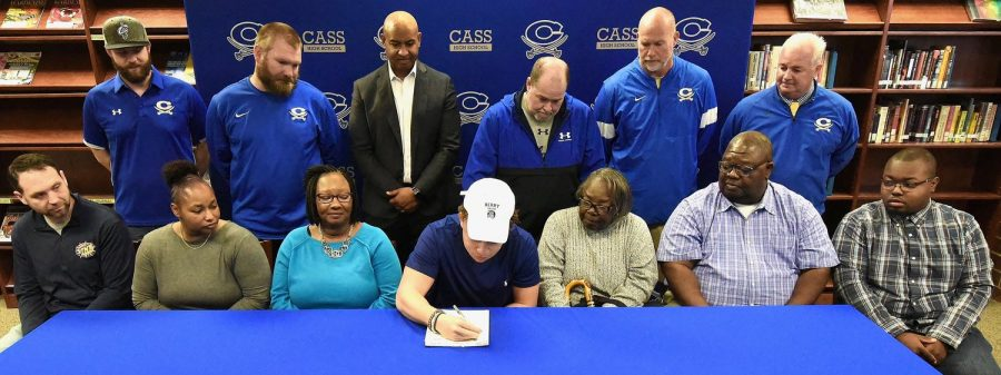 RANDY PARKER/THE DAILY TRIBUNE NEWS Cass High School senior J.P. Perry signed Wednesday to play football at Berry College in Rome. On hand for the signing were, front row, from left: Adam Jernigan, rec. coach; Jackie Cox, aunt; Geri Perry, mother; Sarah Cox, grandmother; Dennis Cox, uncle; and Zach Taylor, cousin.  Back row: P.J. Hughes and Brock Pyle, CHS assistant coaches; Richard Cox, cousin and mentor; Bobby Hughes, CHS head football coach; Jamey Gaddy, CHS assistant coach; and Dr. Nicky Moore, CHS athletic director.